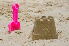 Castillo de arena con una pala Imagenes de archivo