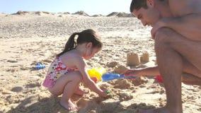 Castillo de arena de la estructura de Helping Daughter To del padre en la playa almacen de metraje de vídeo