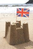 Castillo de arena en la playa con la unión Jack Flag Imagen de archivo