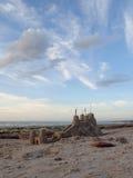Castillo de arena grande en el montón con la fosa, y cielo azul nublado imagenes de archivo
