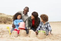 Castillo de arena joven de la fundación de una familia el día de fiesta de la playa Foto de archivo libre de regalías
