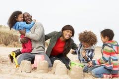 Castillo de arena joven de la fundación de una familia el día de fiesta de la playa Imagenes de archivo