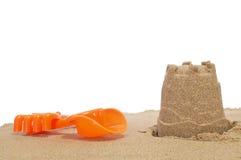 Castillo de arena, pala y rastrillo fotografía de archivo