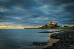 Castillo de Bamburgh en la salida del sol en la costa costa de Northumberland fotos de archivo libres de regalías