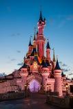 Castillo de Disneylandya París iluminado en la puesta del sol fotos de archivo