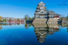 Castillo de Matsumoto con el puente rojo, el cielo azul y la reflexión del Fotos de archivo libres de regalías
