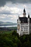 Castillo de Neuschwanstein: Cielos nublados dramáticos con pueblo en fondo Fotografía de archivo libre de regalías