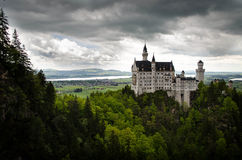 Castillo de Neuschwanstein: Cielos nublados dramáticos con pueblo en fondo Imagen de archivo