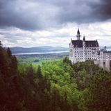 Castillo de Neuschwanstein: Cielos nublados dramáticos con pueblo en fondo Imagen de archivo libre de regalías