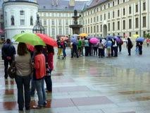 Castillo de Praga, grupo del viaje que abriga debajo de los paraguas en lluvia Foto de archivo