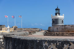 CASTILLO DE SAN FELIPE DEL MORRO, PUERTO RICO, USA - FEB 16, 2015: Lighthouse Tower and stone walkway at fortress lined with flags Stock Photo