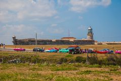 The Castillo Del Morro lighthouse in Havana. Retro vintage cars stand at the entrance. The old fortress Cuba. The Castillo Del Morro lighthouse in Havana. View Royalty Free Stock Photo