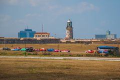 The Castillo Del Morro lighthouse in Havana. Retro vintage cars stand at the entrance. The old fortress Cuba. The Castillo Del Morro lighthouse in Havana. View Stock Photography