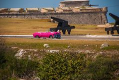 The Castillo Del Morro lighthouse in Havana. Retro vintage cars stand at the entrance. The old fortress Cuba. The Castillo Del Morro lighthouse in Havana. View Royalty Free Stock Image