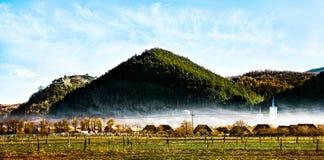 Castillo hermoso en un pico sobre una ciudad y un cemetry debajo del cielo azul Imagenes de archivo
