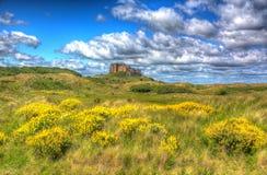 Castillo Northumberland de Bamburgh en una colina con el cloudscape en hdr imagen de archivo