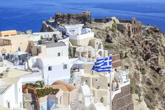 Castillo område med slotten och byzantine fördärvar och den grekiska flaggan i oia arkivfoto