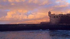 Castillo por el mar en puesta del sol almacen de video