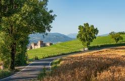 Castillo rodeado por los campos verdes y los campos de trigo en Italia imágenes de archivo libres de regalías