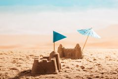 Castillos de arena con la bandera y el paraguas en la playa Fotos de archivo