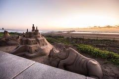 Castillos de arena en una playa en la salida del sol Imágenes de archivo libres de regalías