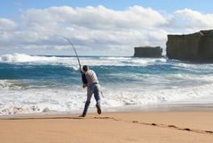 Casting. Retired guy enjoying leisure time on the beach. Slight motion blur on rod Royalty Free Stock Images