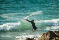 Casting For Baitfish. A fisherman throwing a cast net for bait fish before heading offshore for a day of fishing in the Atlantic Ocean off of Florida`s South Royalty Free Stock Photo