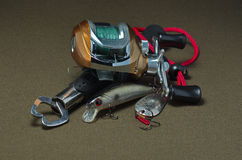 Casting fishing reel on a dark background. Casting fishing reel with lures and capture on a dark background Stock Images