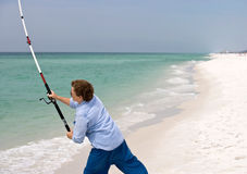 Casting Off. Mature woman casting her fishing line into the surf...moments later she caught a nice pompano royalty free stock photo