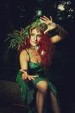 Casting a spell. Redhead witch casting a spell in the forest stock photo