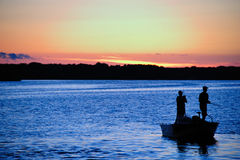 Casting At Sunset in Wisconsin. Silhouette of Fishermen Hoping For Their Last Catch At Sunset in Wisconsin stock image