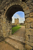 Castle. The tower of an ancient castle, viewed through a stone arch Stock Photography