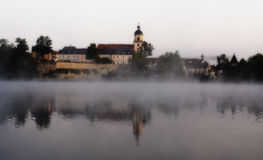 Castle above the lake in a fog. Castle above the lake in the morning mist Royalty Free Stock Photo