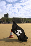 Castle and beach with jolly roger flag Stock Photography