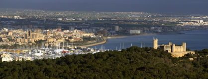 Castle of Bellver, Majorca. Castle of Bellver in Majorca, Spain, seen from a distance, city and harbor to left, trees in foreground Royalty Free Stock Images