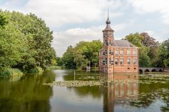 Castle Bouvigne reflected in the moat. Kasteel Bouvigne is a 15th century brick castle south of the Dutch city of Breda. The romantic-looking castle was stock photo