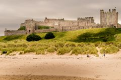 A view of an ancient castle on top of a grass hill. A castle from a bygone age on a grass hill. a view of castle from the beach. grey clouds gathering in the sky stock images