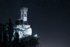 Castle on cliff with clock tower stock photography