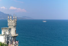 Castle on cliff, ship and sea. Authentic small castle on cliff over sea and white sail cruise boat. crimea, ukraine Stock Photography