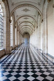 Castle corridor. View of a corridor of a french castel with a black and white Checkerboard ground in marble and big arcs It is Arras city in France stock photos