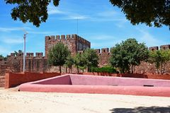 Castle courtyard and battlements, Silves, Portugal. Courtyard and gardens of the Medieval castle with battlements and tower to the rear, Silves, Portugal royalty free stock images