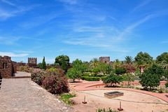 Castle courtyard and gardens, Silves, Portugal. View of the gardens within the Medieval castle with battlements and towers to the rear, Silves, Portugal, Europe Royalty Free Stock Image