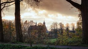 The castle Doorwerth that can be seen behind a row of trees under a spectacular sky royalty free stock image