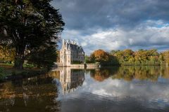 The castle. Castle on the edge of a lake. Autumn picture with a cloudy sky. Nature an trees. Peaceful place royalty free stock photos