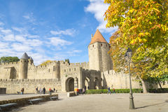 Castle or fort know as La Cite de Carcassonne, France. Carcassonne, France - October 20, 2016; Tourists arriving at stone wall and turrets at drawbridge entrance Stock Photos