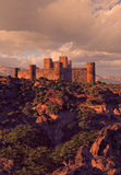 Castle Fortress In The Mountains. Castle in the mountains near a lake with rock formations and trees, brought out by the evening sun light Royalty Free Stock Images