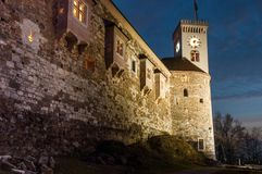 Castle fortress wall and clock tower at night. Castle fortress wall at night with clock tower and blue night sky. Ljubljana Slovenia royalty free stock images