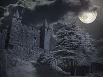 Castle in a full moon night. Medieval castle in a cloudy full moon night royalty free stock photos