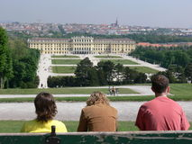 Castle garden. Three people sitting on a bench in the castle garden of vienna stock image