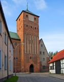 Castle gate, gothic style. A castle gate, tall, red brick, gothic style, a checked house at the right Royalty Free Stock Photography